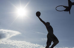 Silhouette basketball player in mid air about to slam dunk. A silhouette of a basketball player in mid air about to dunk the ball on an outdoor court Stock Images