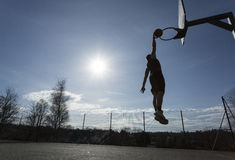 Silhouette basketball player in mid air about to slam dunk Royalty Free Stock Photo