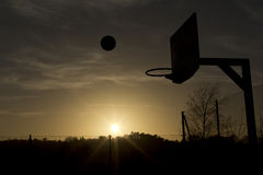 Silhouette of basketball shot with the sun setting Stock Photography