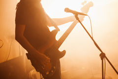 Silhouette of bass guitar player. On the stage with microphone and bright warm illumination, live music theme Stock Image