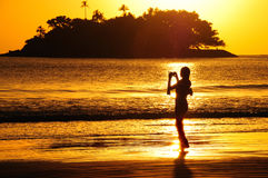 Silhouette on the beach. Silhouette of girl photographing the sunrise on the beach Royalty Free Stock Photo