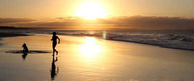 Silhouette beach image at sunset. Silhouetted image of kids playing on beach in Mozambique at sunset Stock Photos