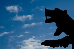 Silhouette of a bear. Against blue cloudy sky Stock Images