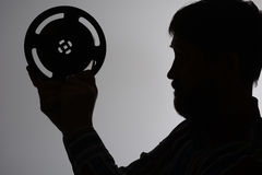 Silhouette of a bearded man looks at 16mm Royalty Free Stock Photos