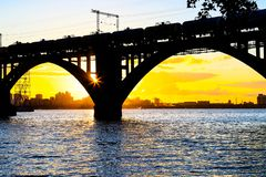 Silhouette of a beautiful arched railway bridge and wagons on the Dnieper river at sunset. Dnipropetrovsk. Dnepr, Dnipro, Dnepropetrovsk Ukraine stock image