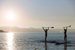 Silhouette of beautiful couple with sup surf and paddle in hands at the ocean. Concept lifestyle, sport, love Royalty Free Stock Image