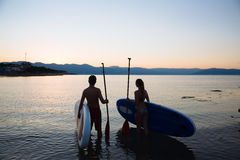 Silhouette of beautiful couple with sup surf and paddle at the ocean. Concept  lifestyle, sport, love Stock Images