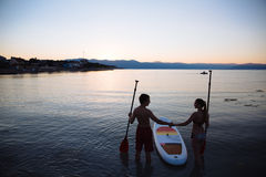 Silhouette of beautiful couple with sup surf and paddle at the ocean. Concept lifestyle, sport, love Stock Photo