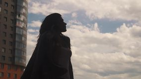 Silhouette of beautiful girl on a background of sky, clouds and modern buildings. Slow motion. Portrait of a beautiful young girl walking through the city among stock video