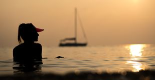 Silhouette of a beautiful girl bathing in the sea on her yacht in the rays of the setting sun. Holiday in Thailand.  Royalty Free Stock Images