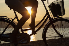 Silhouette of a beautiful girl on a bicycle. Silhouette of a beautiful girl on the old bike rides along the beach sunrise royalty free stock photography