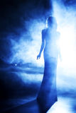 Silhouette of the beautiful girl in blue theatrical fog. Stock Photo