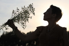 A silhouette of a beautiful girl holding flowers Stock Photo