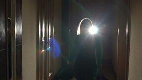 Silhouette of girl running in dark through tunnel.