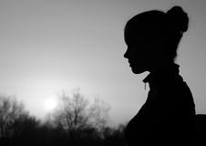 Silhouette of the beautiful girl in the nature at summer sunset Royalty Free Stock Images