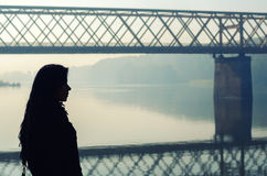 Silhouette of beautiful girl standing on dock with bridge. In background on sunny autumn day Royalty Free Stock Photos