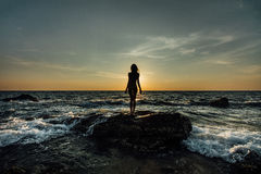 Silhouette of a beautiful girl at sunset by the sea, on a sea stone in a swimsuit. Waves, foam. Royalty Free Stock Images