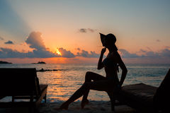 Silhouette of a beautiful slender girl on a sunset background and sun loungers on the ocean shore. Woman watch skyline Royalty Free Stock Photos