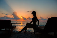 Silhouette of a beautiful slender girl on a sunset background and sun loungers on the ocean shore. Woman watch skyline Stock Image
