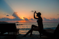 Silhouette of a beautiful slender girl on a sunset background and sun loungers on the ocean shore. Woman watch skyline Stock Photo