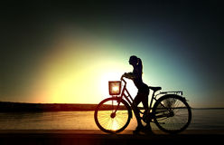 Silhouette of the beautiful straight woman. Shape of the beautiful young woman with bicycle on sunrise near a sea Royalty Free Stock Photography