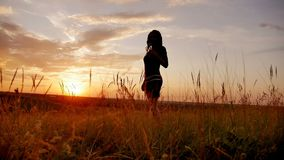 Silhouette of a beautiful teen girl standing on a background of gorgeous sunsets stock footage