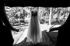 Silhouette of beautiful wedding dress hanging on the wooden arbor. Outdoors royalty free stock photos