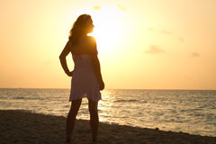 Silhouette of beautiful woman. On the beach at sunrise Stock Image