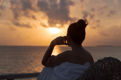 Silhouette of a beautiful woman contemplating sunrise from a balcony over the sea royalty free stock image