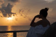 Silhouette of a beautiful woman contemplating sunrise from a balcony over the sea royalty free stock photo