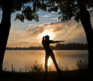 Silhouette of a beautiful woman doing yoga exercis. E on the riverside Stock Photo