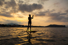 Silhouette of a beautiful woman on Stand Up Paddle Board. SUP Stock Image