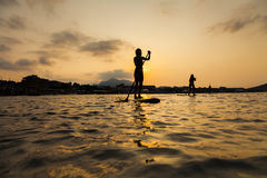 Silhouette of a beautiful woman on Stand Up Paddle Board. Stock Photos
