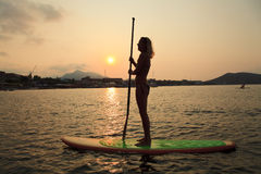 Silhouette of a beautiful woman on Stand Up Paddle Board. SUP Stock Photo