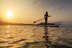 Silhouette of a beautiful woman on Stand Up Paddle Board. Stock Photography