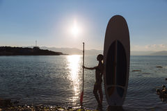 Silhouette of a beautiful woman on stand up paddle board. SUP, concept lifestyle, sport. Silhouette of a beautiful woman on stand up paddle board. SUP, concept Stock Photos