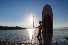 Silhouette of a beautiful woman on stand up paddle board. SUP, concept  lifestyle, sport. Silhouette of a beautiful woman on stand up paddle board. SUP, concept Royalty Free Stock Photos