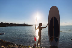 Silhouette of a beautiful woman on stand up paddle board. SUP, concept  lifestyle, sport. Silhouette of a beautiful woman on stand up paddle board. SUP, concept Stock Photography