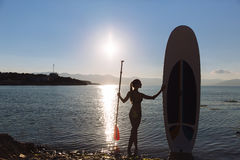 Silhouette of a beautiful woman on stand up paddle board. SUP, concept  lifestyle, sport. Silhouette of a beautiful woman on stand up paddle board. SUP, concept Stock Image
