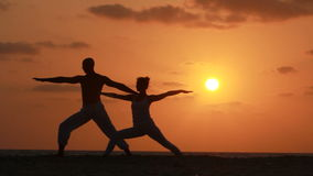 Silhouette of a beautiful Yoga couple stock video footage