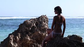Silhouette of a beautiful Yoga woman in the morning on a beach rock by the ocean. Sexy young woman in swimwear. Tatoo on. Silhouette of a beautiful Yoga woman in stock video