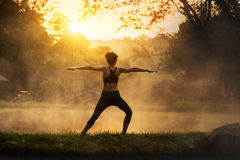 Silhouette of a beautiful Yoga woman in the morning at the hot spring park Royalty Free Stock Photography