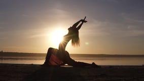 Silhouette of beautiful yoga woman in the morning sky on a sea beach. A woman practicing yoga Virabhadrasana II Warrior