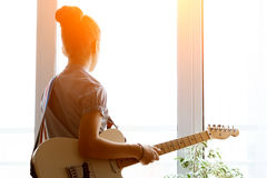 Silhouette beautiful young girl with guitar. Silhouette of a beautiful young girl with a guitar near the window Royalty Free Stock Photography