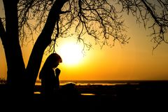 Silhouette of woman praying to God in the nature witth the Bible at sunset, the concept of religion and spirituality. Silhouette of beautiful young woman praying Stock Photography