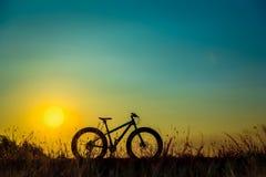 Silhouette beaux ciel de coucher du soleil et vélo de montagne Photo libre de droits
