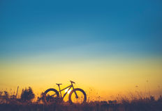 Silhouette beaux ciel de coucher du soleil et vélo de montagne Photographie stock libre de droits