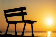 Silhouette of a bench against sunset Stock Images