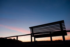Silhouette of bench at sunset Stock Photo