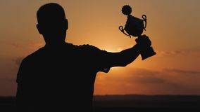 Silhouette best man Winner Award victory trophy for professional champion challenge holding trophy cup over head with